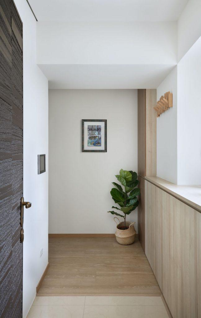 木地板與地磚高低差正好成為入口落塵區,阻絕砂塵入室內。在柱面設置外出衣架,造型美觀又實用