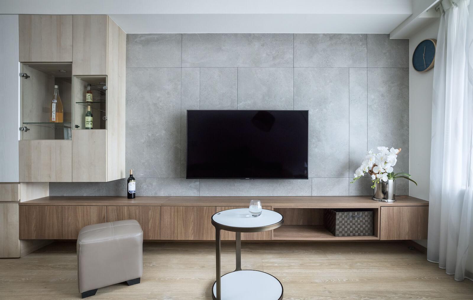 客廳電視牆以灰色磁磚拼貼,搭配深、淺色系系統櫃,成為最吸睛牆面。